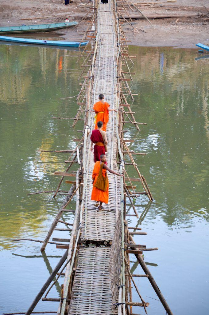 Novice monks crossing the bamboo bridge in Luang Prabang, Laos