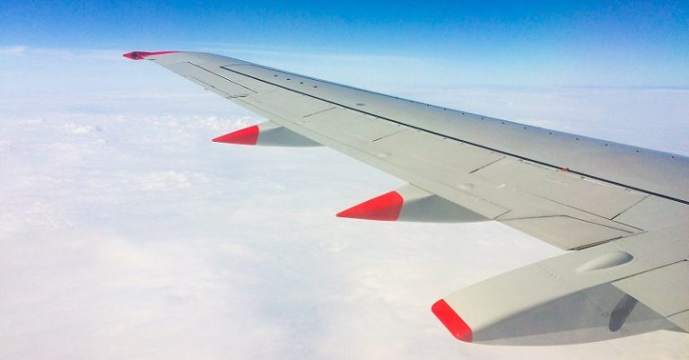 Wing of a plane over clouds and blue sky