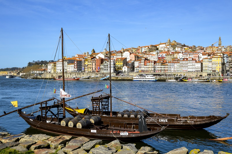 Two small Port boats on a bright blue river with a picturesque view of colorful houses behind in Porto, Portugal