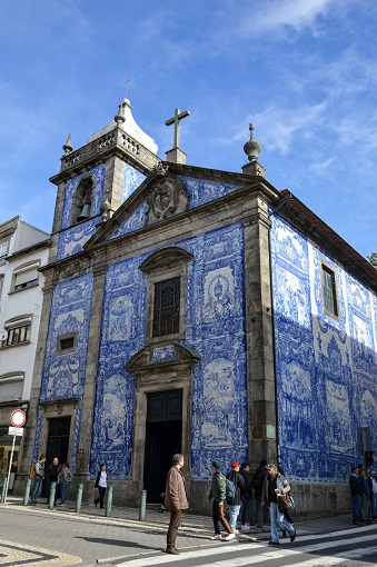 Facade of the Chapel of Souls decorated with blue and white azulejo tiles in Porto