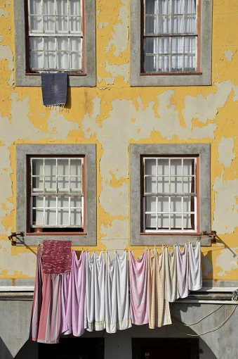 Laundry hanging in front of a yellow building in Porto
