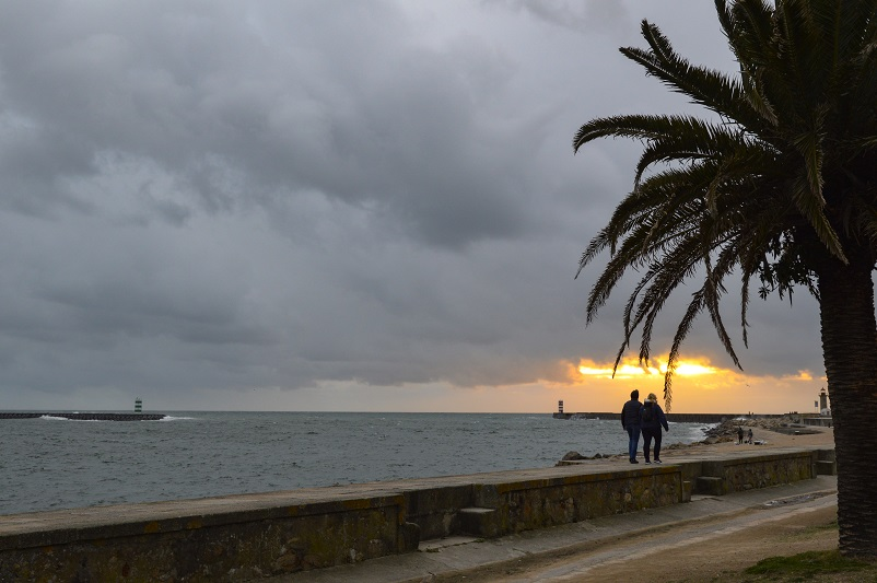 Two people walking along the Atlantic Ocean in Foz do Douro in Porto, Portugal