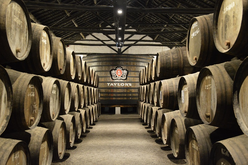 Port wine barrels lining a dark cellar with a Taylor's sign at the back in Porto
