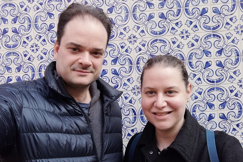 Sarah and Justin smiling in front of blue and white tiles in Porto